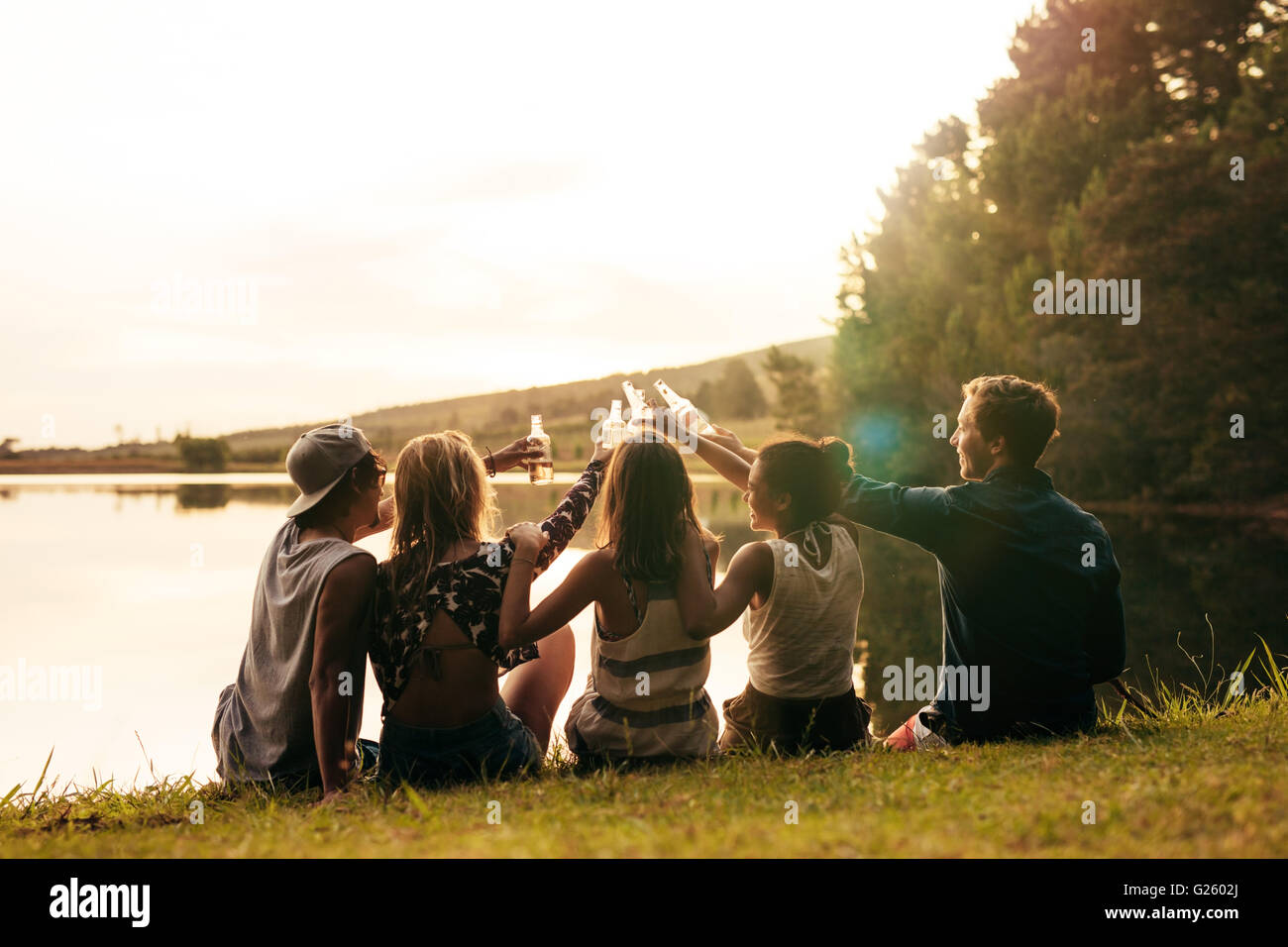 Group of young people sitting in a row at a lake with beers. Young friends toasting and celebrating with beers at - Stock Image