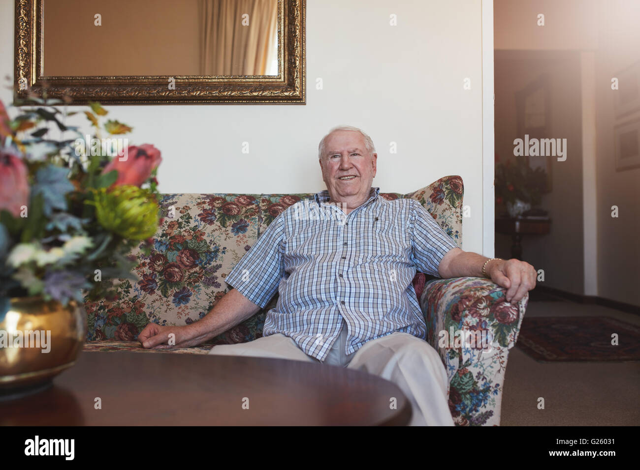 Indoor shot of happy senior man sitting relaxed on a couch at old age home. He is looking at camera and smiling. - Stock Image