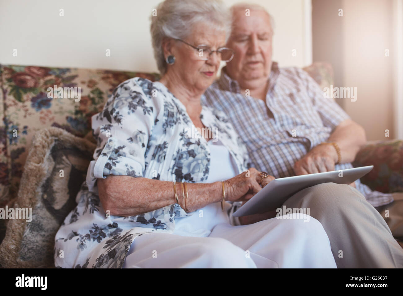 Portrait of old woman sitting with her husband and using digital tablet. Senior couple sitting on sofa at home with - Stock Image