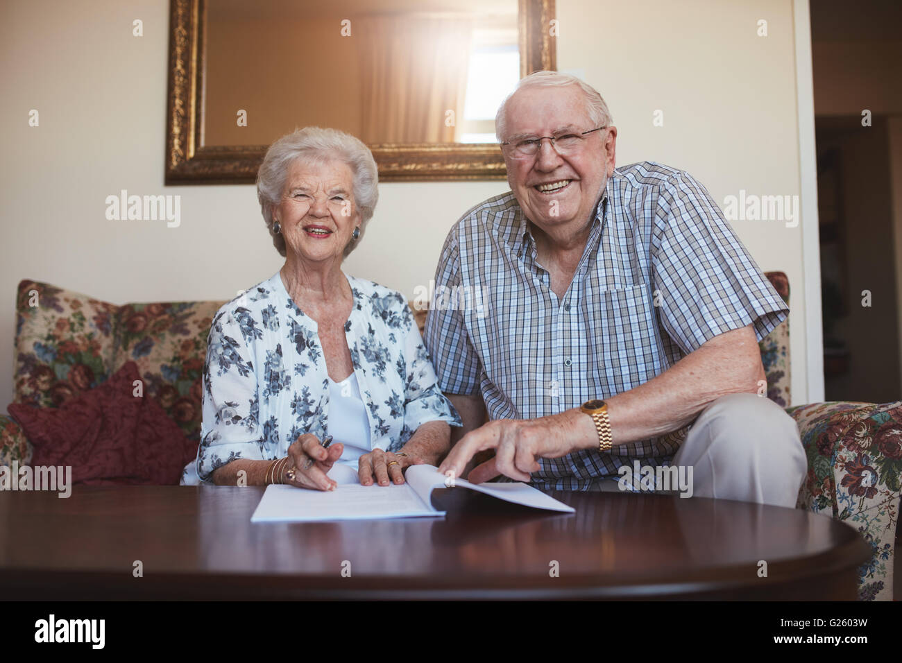 Portrait of a smiling retired couple looking over documents. Senior caucasian man and woman sitting on sofa at old - Stock Image