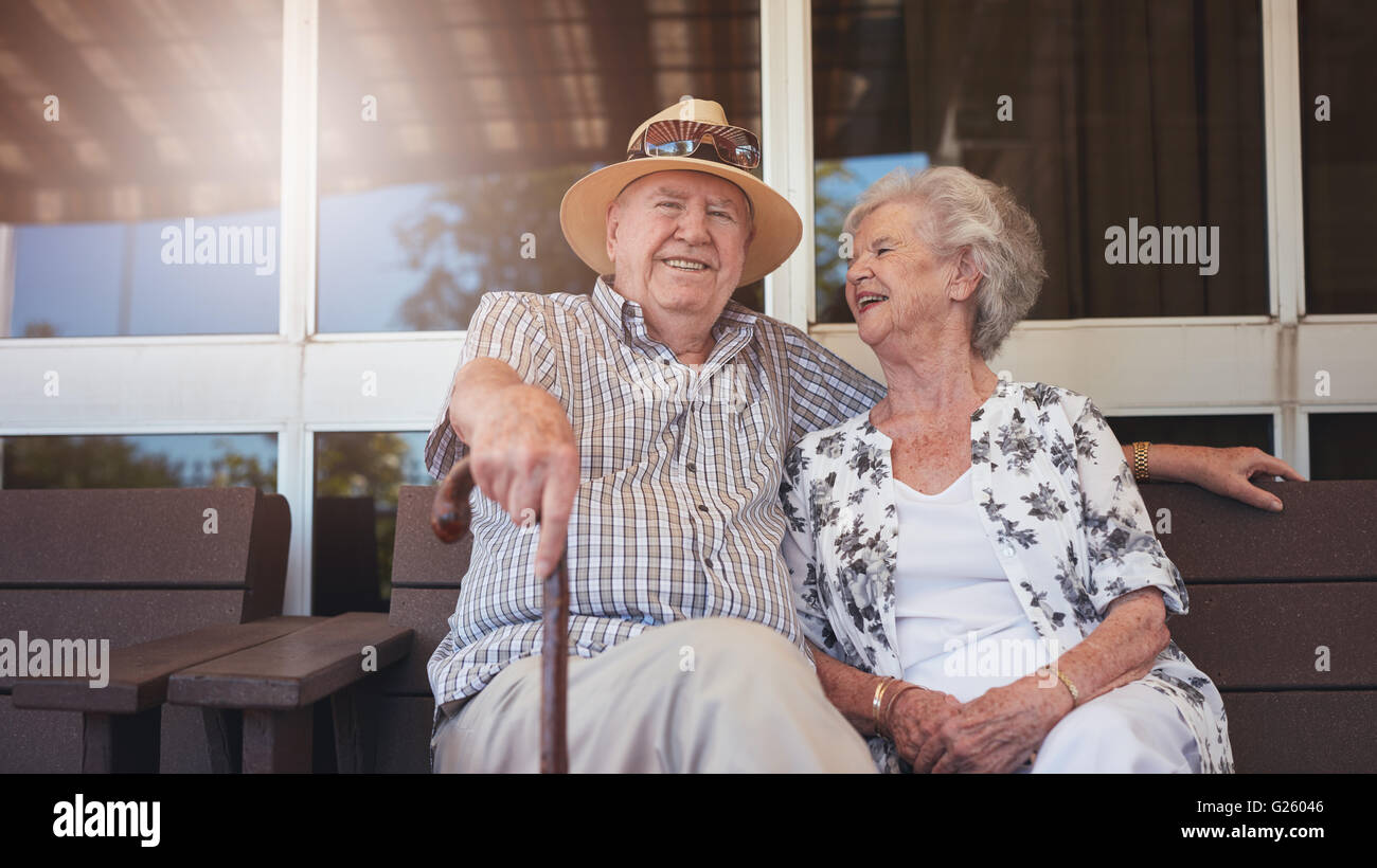 Portrait of handsome senior man sitting with his wife on a bench outside their house. Retired couple taking a break - Stock Image