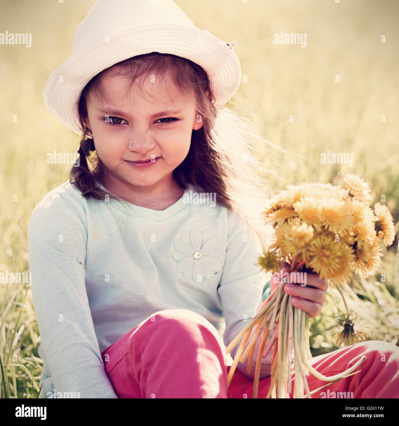 Funny grimacing kid girl in fashion hat sitting on the grass and holding yellow flowers. Toned closeup portrait - Stock Image