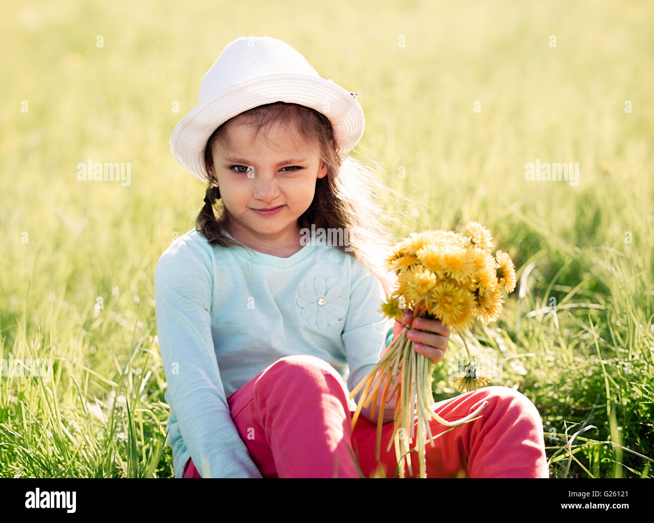 Funny grimacing kid girl in fashion hat sitting on the grass and holding yellow flowers - Stock Image