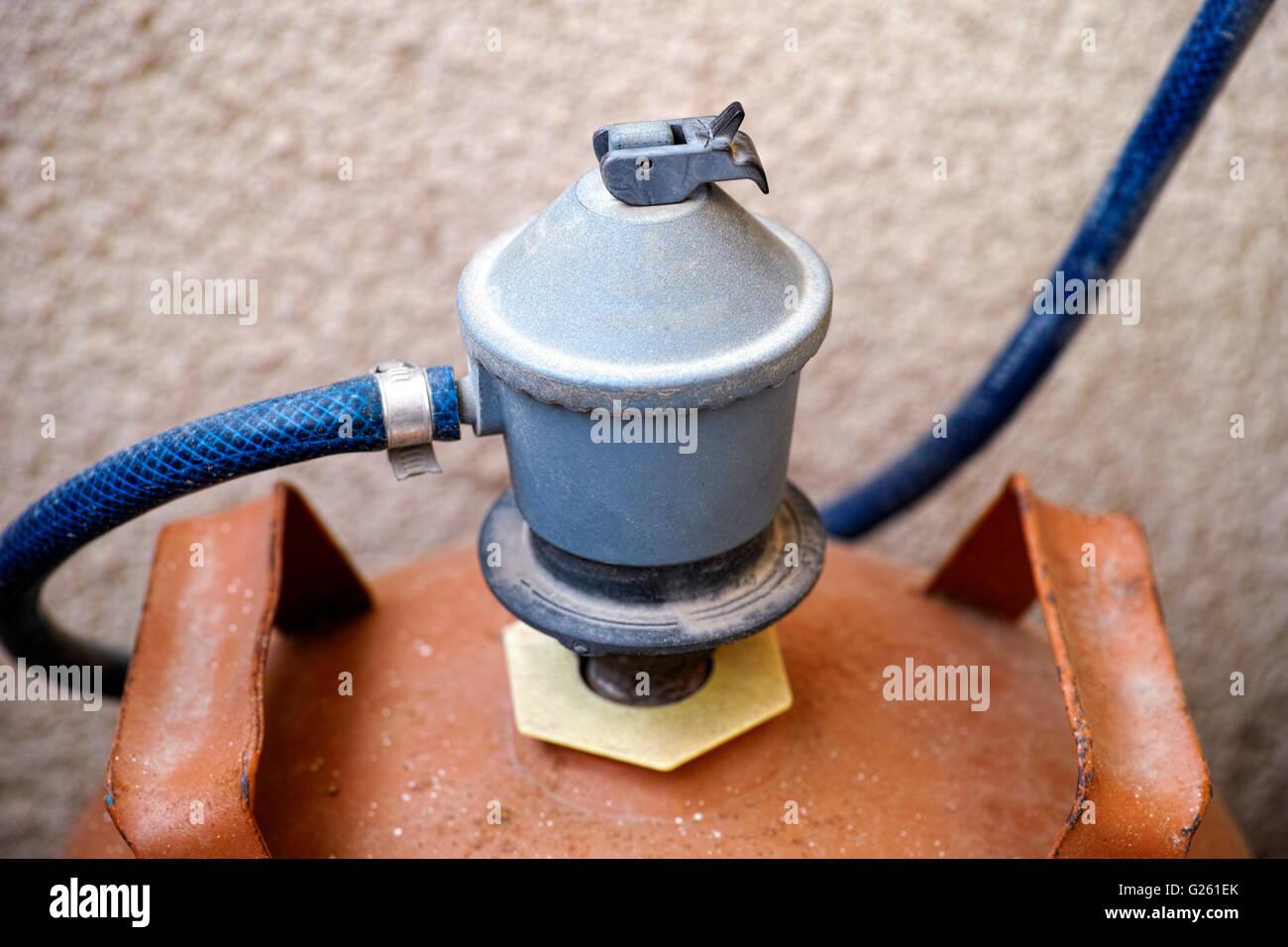Gas regulator switch on orange gas bottle. - Stock Image