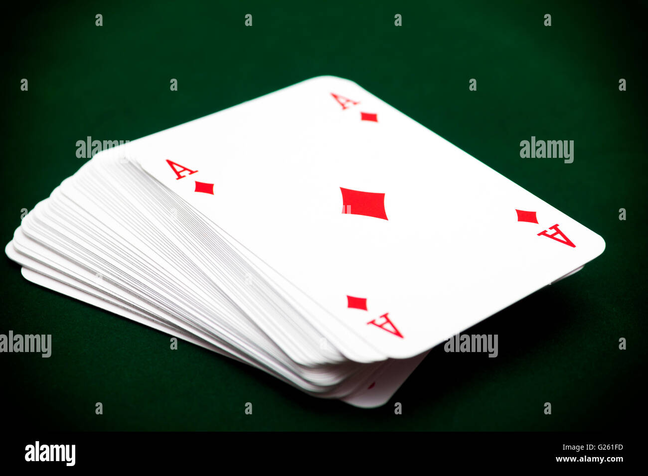 Deck of cards with ace of diamond on top. Green background - Stock Image