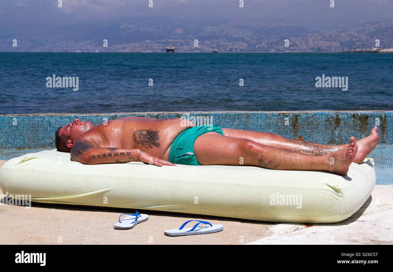 Beirut, Lebanon. 25th May 2016. A sunbather on an inflatable sun bed lies by the seafront on a hot day in the Lebanese - Stock Image