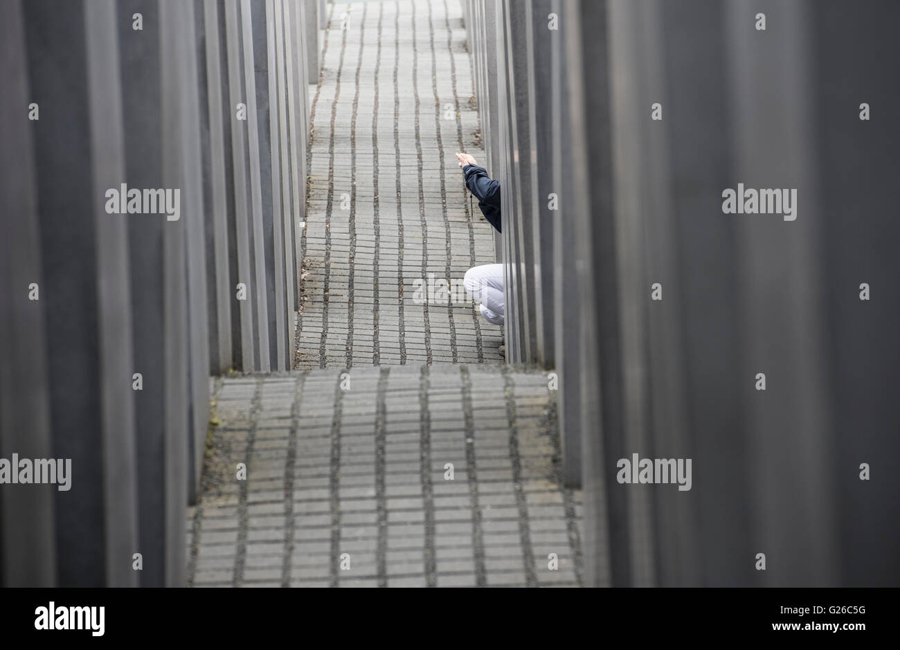 Berlin, Germany. 25th May, 2015. A woman kneels between the steles of the Holocaust Memorial in Berlin, Germany, Stock Photo