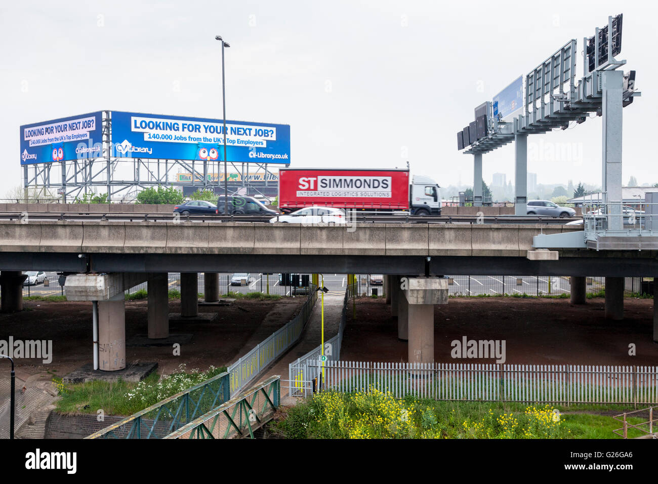 M6 motorway with a road sign gantry and high level electronic advertising billboard, Bescot, Walsall, West Midlands, Stock Photo