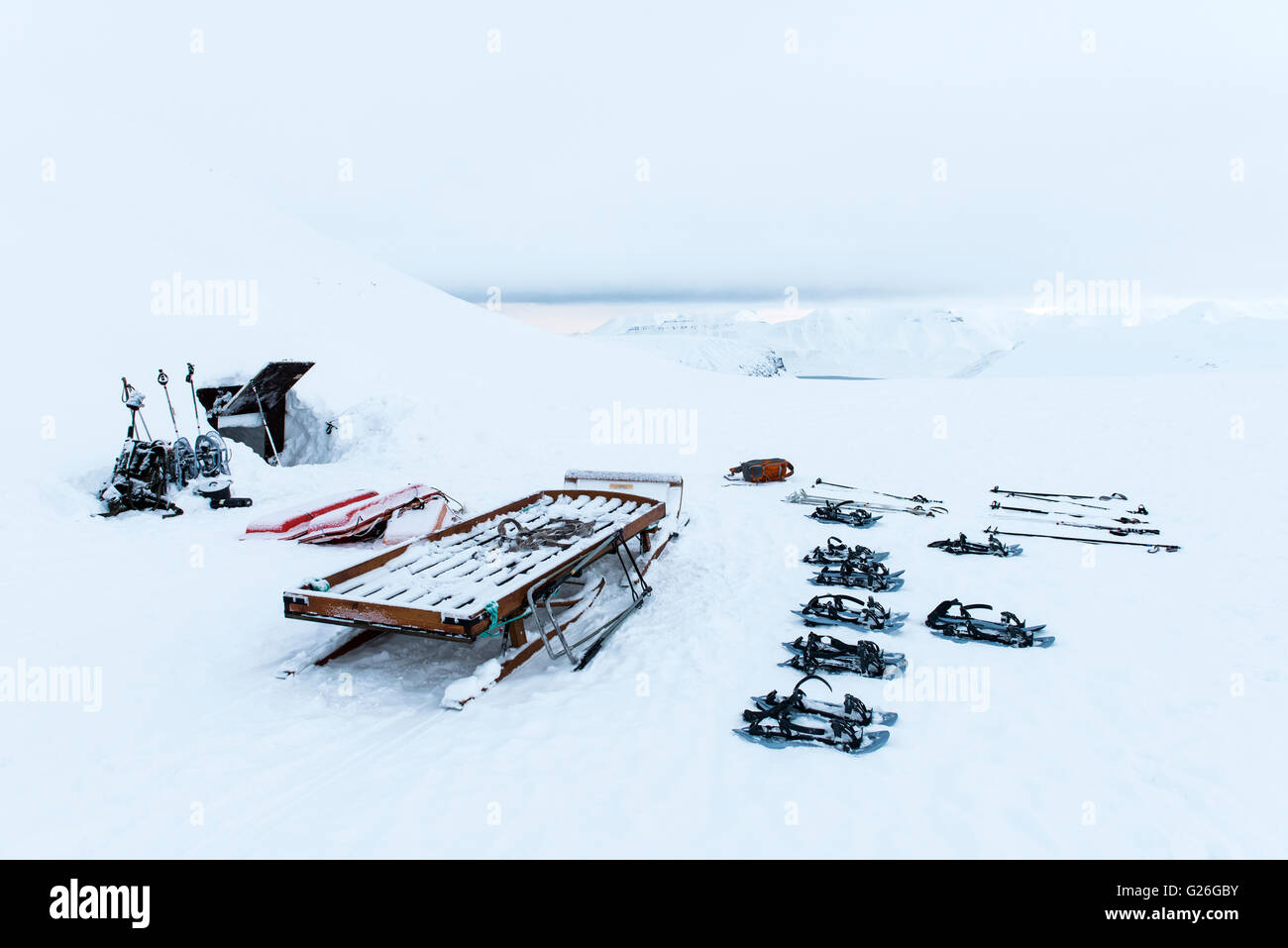 Ski equipment at the entrance of ice cave with snow-capped mountains Longyearbyen, Svalbard, Spitsbergen, Norway - Stock Image