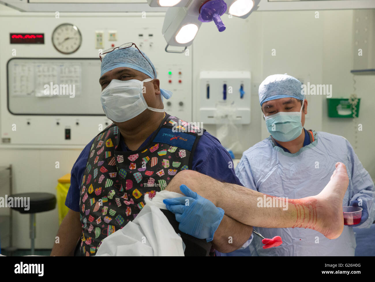 Theatre technicians prepare the patient for an operation - Stock Image