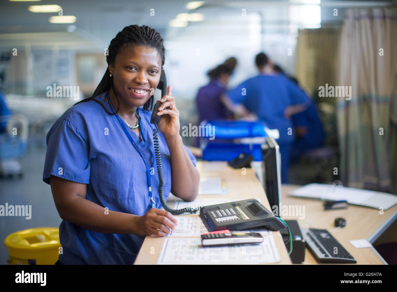 Hospital nurse at a workstation in a ward answering enquiries and checking medical records - Stock Image