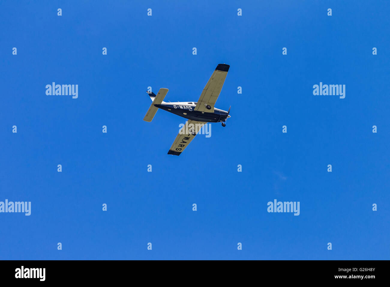 Piper PA-28 G-WARS flying, in a cloudless blue sky, over Elstree Airfield, Hertfordshire, UK, prior to landing. - Stock Image