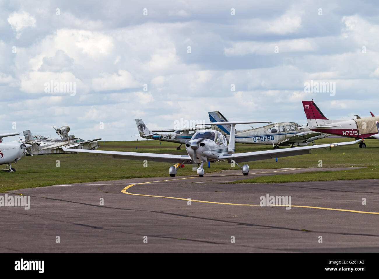 A low winged, high tailed monoplane taxis past some less well used light aircraft at Elstree Airfield, Hertfordshire, - Stock Image
