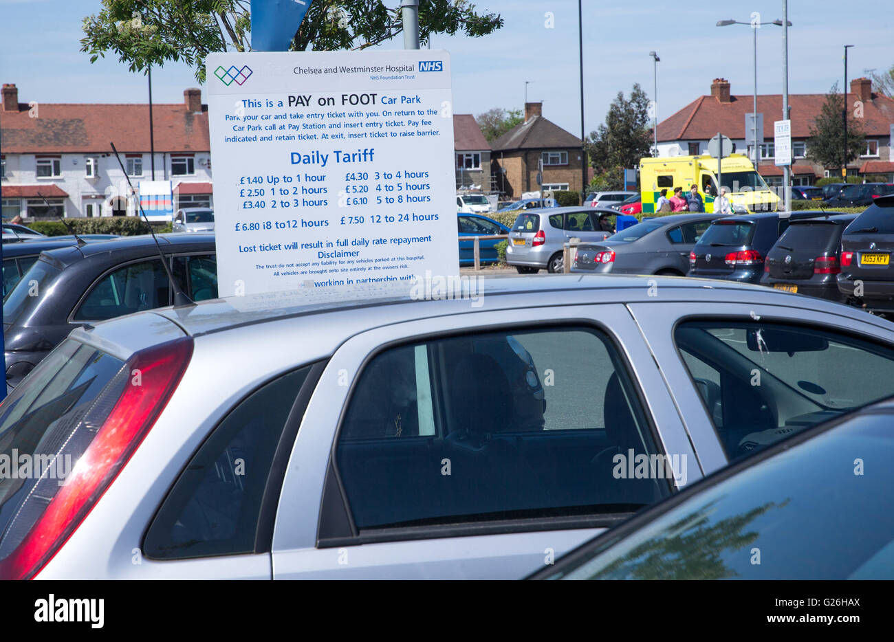 Sign displaying hospital car parking charges and hourly rate for visitors and NHS staff Stock Photo