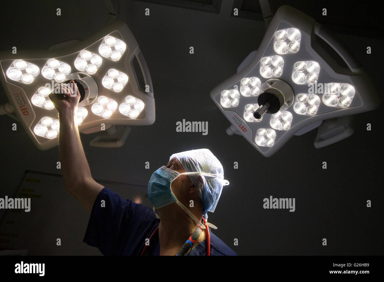 A theatre technician adjusts the lights prior to an operation. - Stock Image