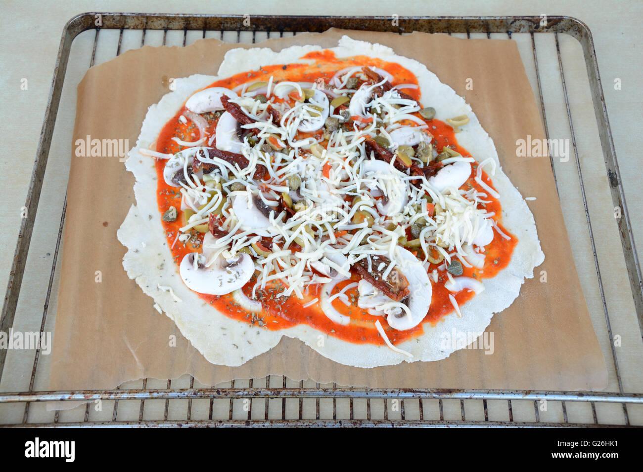 Irregular shape raw pizza before baking - close up - Stock Image
