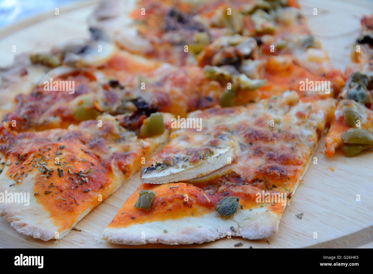 Pizza on wooden plate - close up - Stock Image