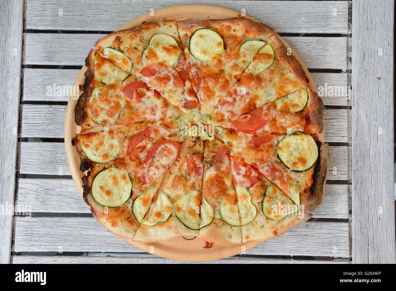 Home made pizza on wooden table - Stock Image