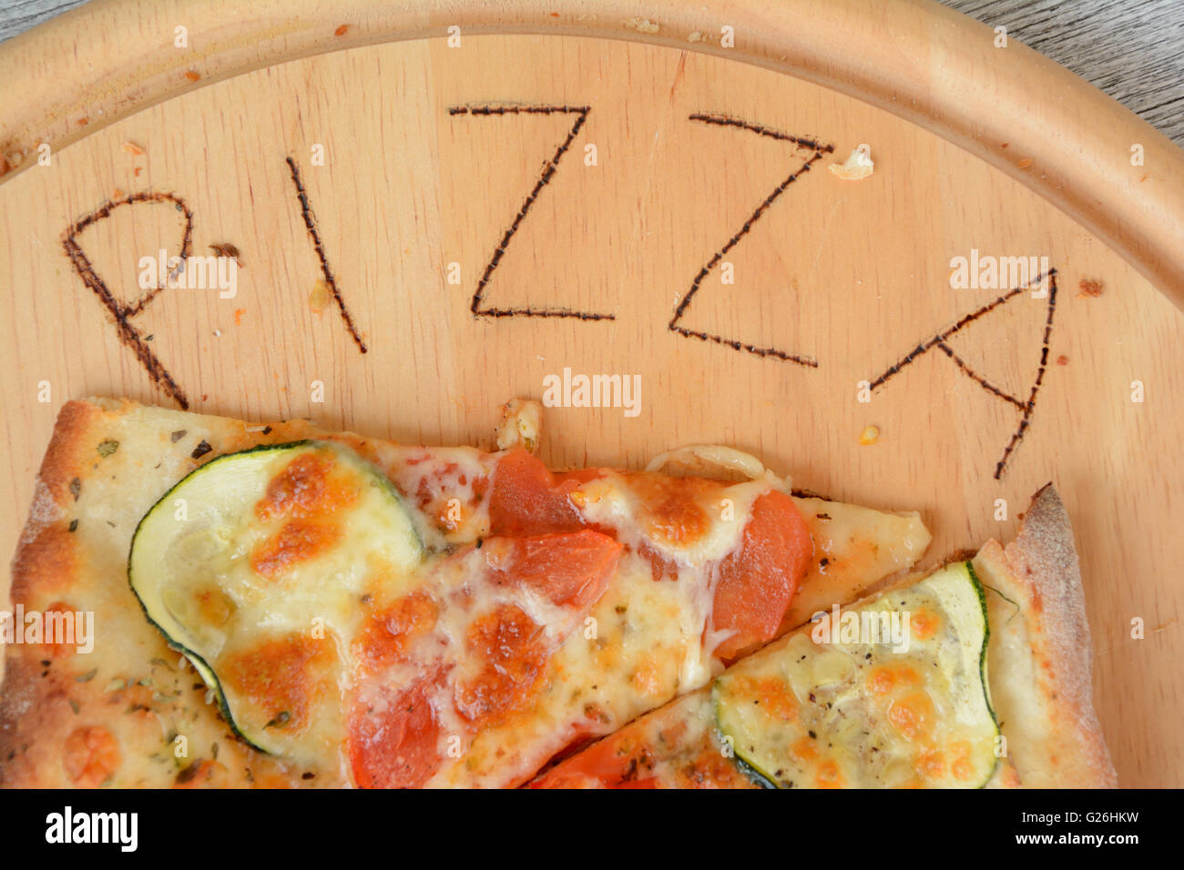 Pizza and pizza word scorched on round wooden plate - Stock Image