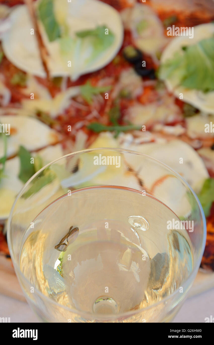 Glass of white wine close up and blurred pizza in background - Stock Image