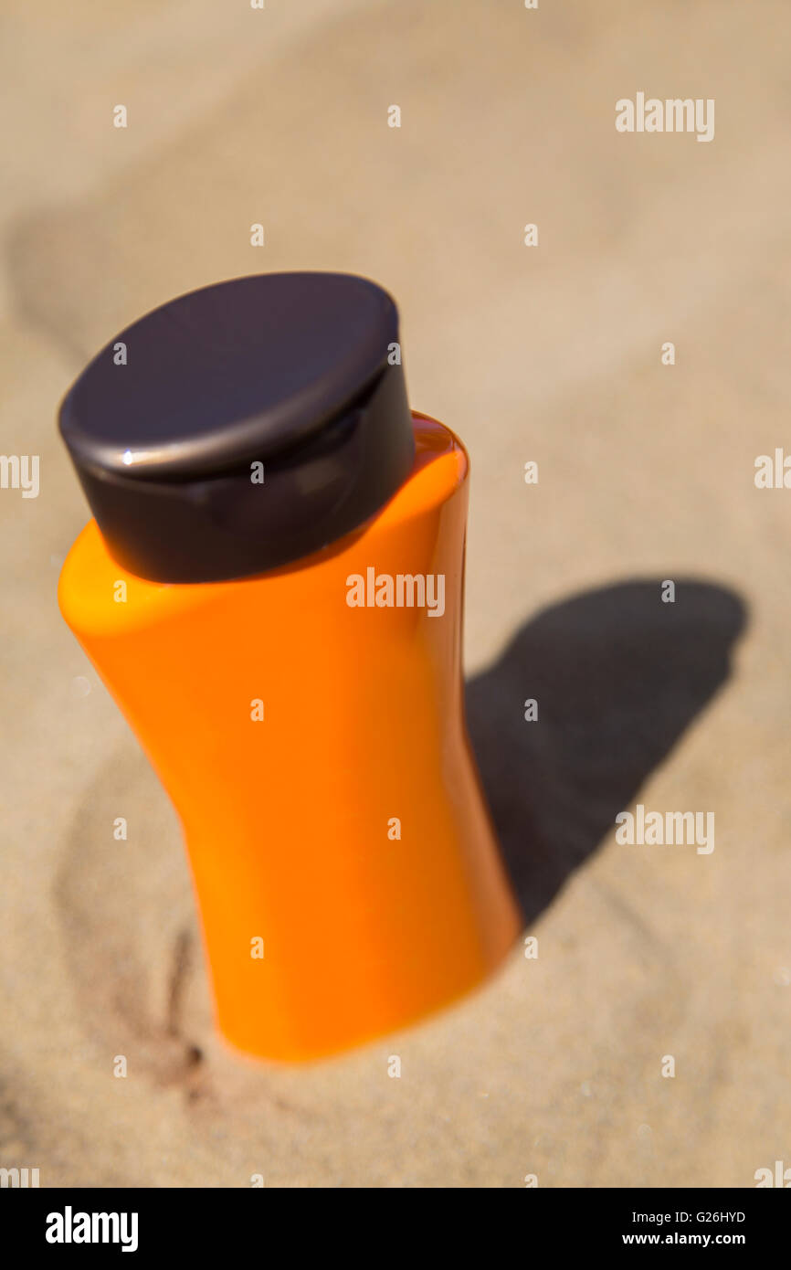 Close up view at   plastic bottles of suncream in sand - Stock Image