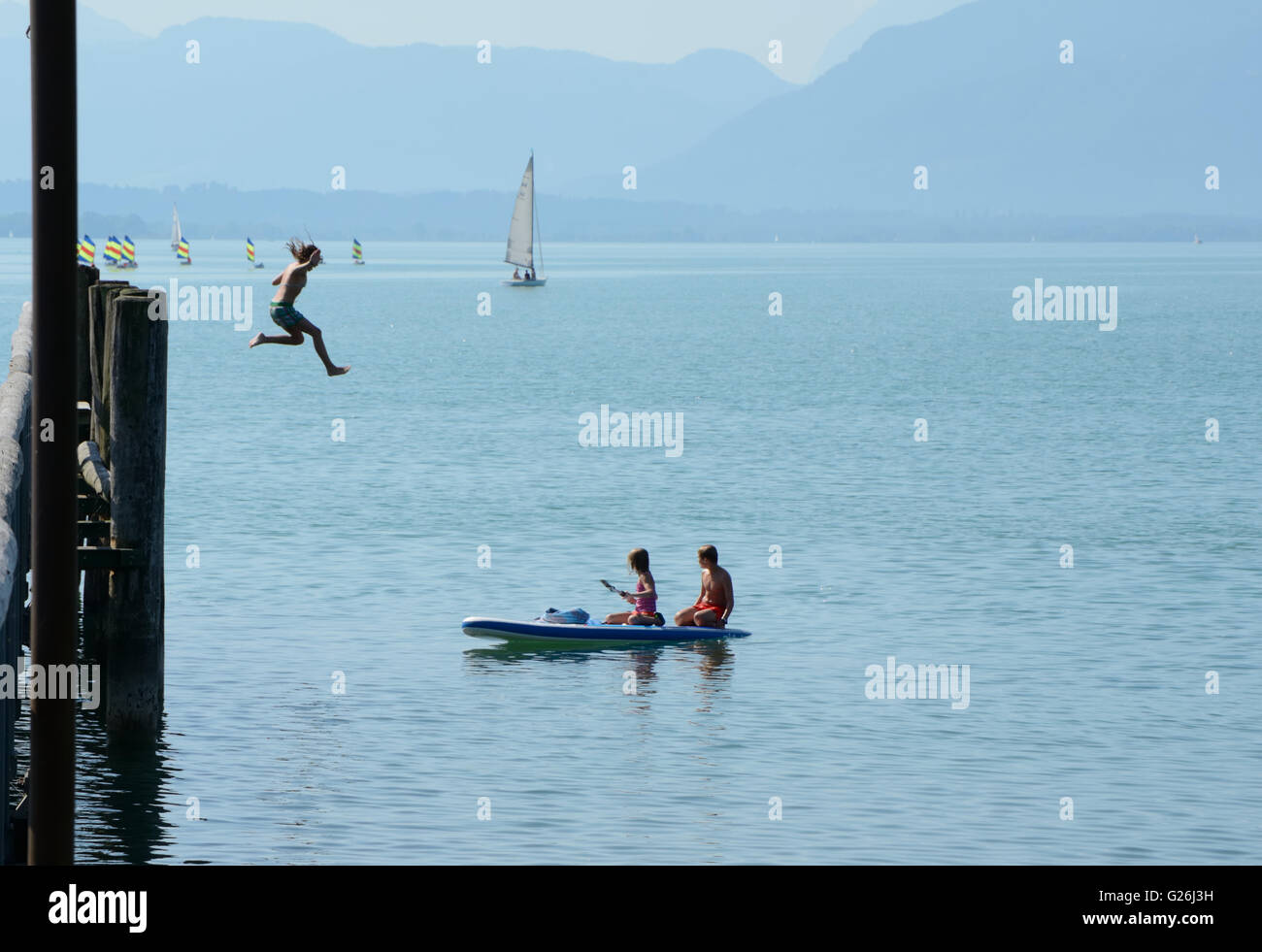 Seebruck, Germany - September 1, 2015: Two unidentified kids on kayak and girl jumping from high pier to water in Stock Photo