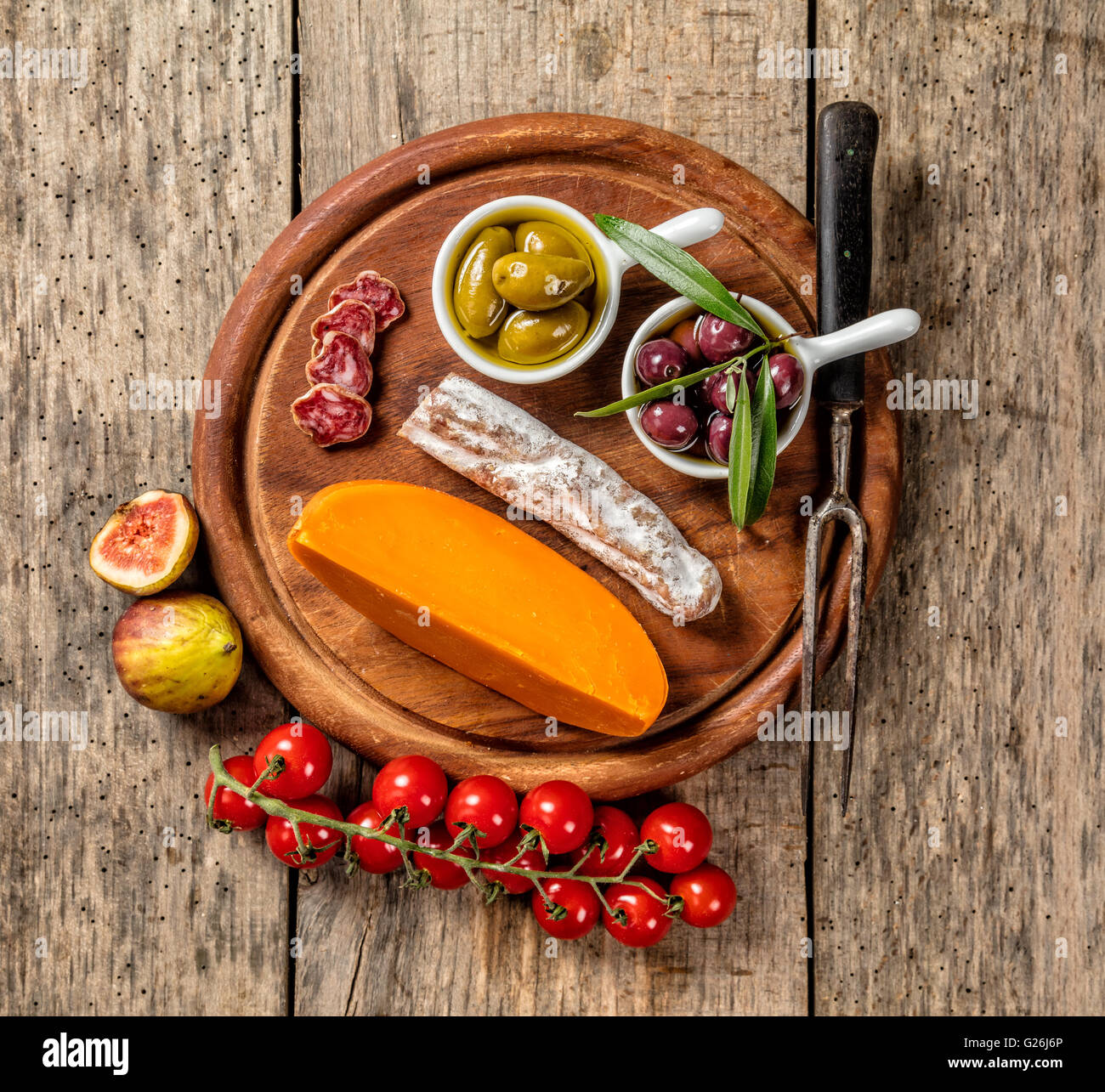 Various kind of traditional cheese and delicacy suitable for wine, placed on wooden cutting board, shot from high - Stock Image