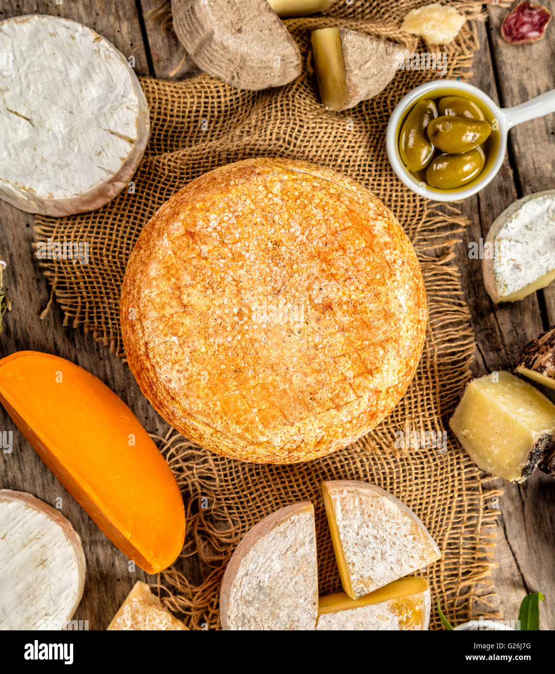 Various kind of traditional cheese and delicacy suitable for wine, placed on wood, shot from high angle view. - Stock Image