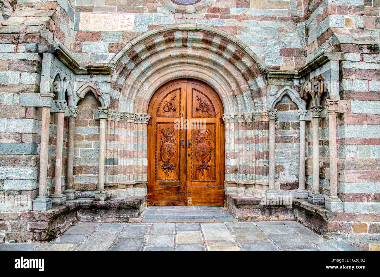 carved wood door at the entrance of the Sacra of Saint Michael church. - Stock Image