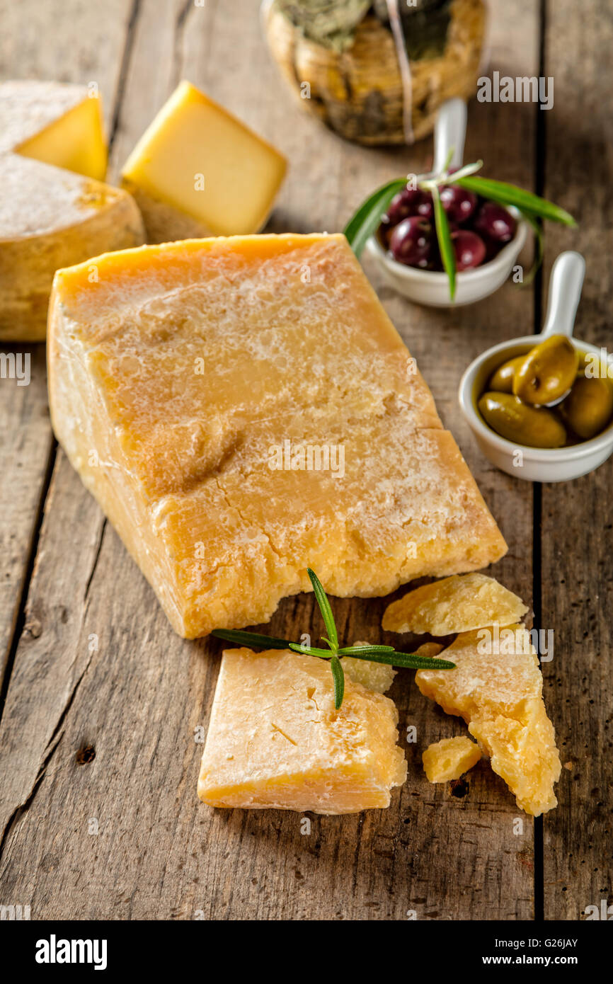 Parmesan cheese on cutting board placed on wood, low depth of focus - Stock Image