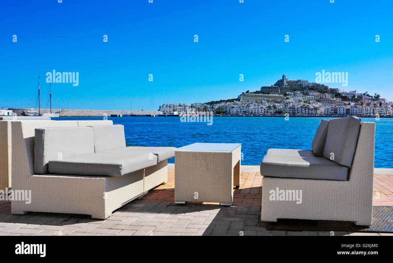 empty couches at the Mediterranean Sea, with Sa Penya and Dalt Vila districts, the old town of Ibiza Town in the - Stock Image