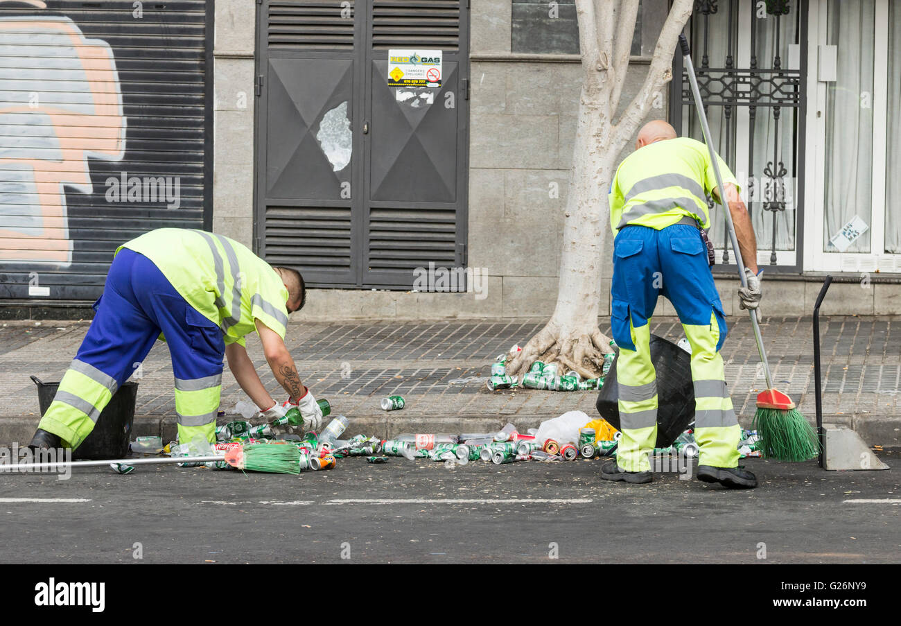 Council workers cleaning up beer cans and plastic cups in street outside football stadium in Spain - Stock Image