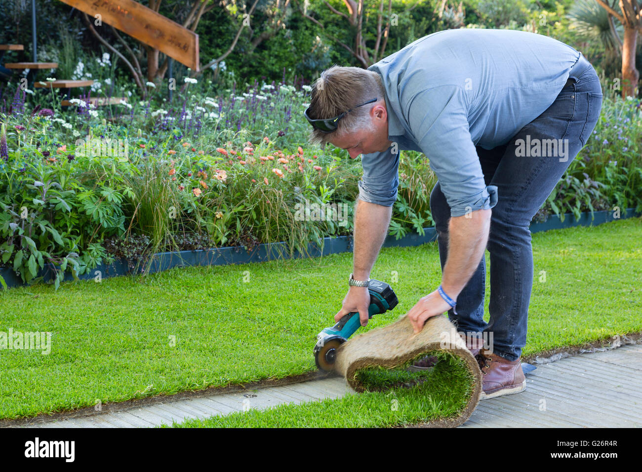 Chelsea Flower Show, London, UK. A worker employs an angle grinder to cut the grass at his stand. - Stock Image