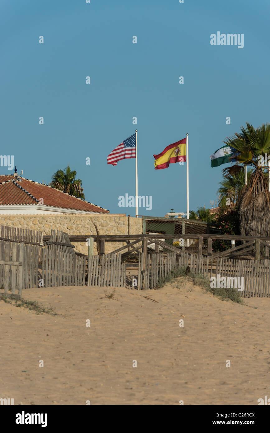 Spanish and USA flags near at the beach near Rota, Cadiz. - Stock Image