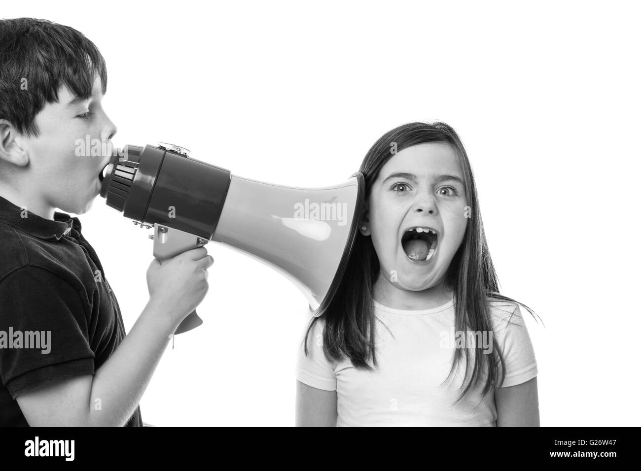 young boy using s megaphone to speak to his friend - Stock Image