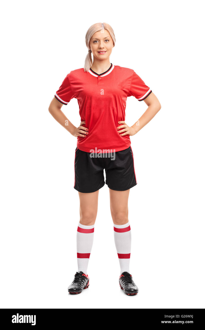 Full length portrait of a professional female soccer player in a red jersey isolated on white background - Stock Image