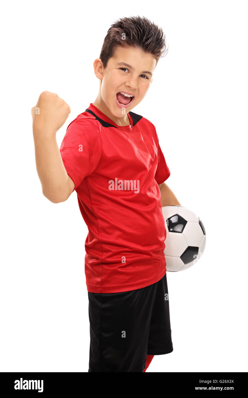 Vertical shot of a joyful junior football player with gripped fist isolated on white background - Stock Image