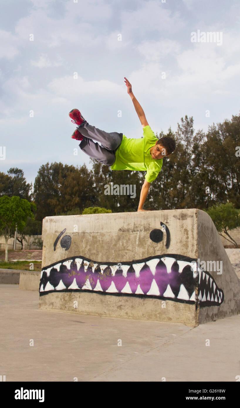Parkour jump teenager in skate park - Stock Image