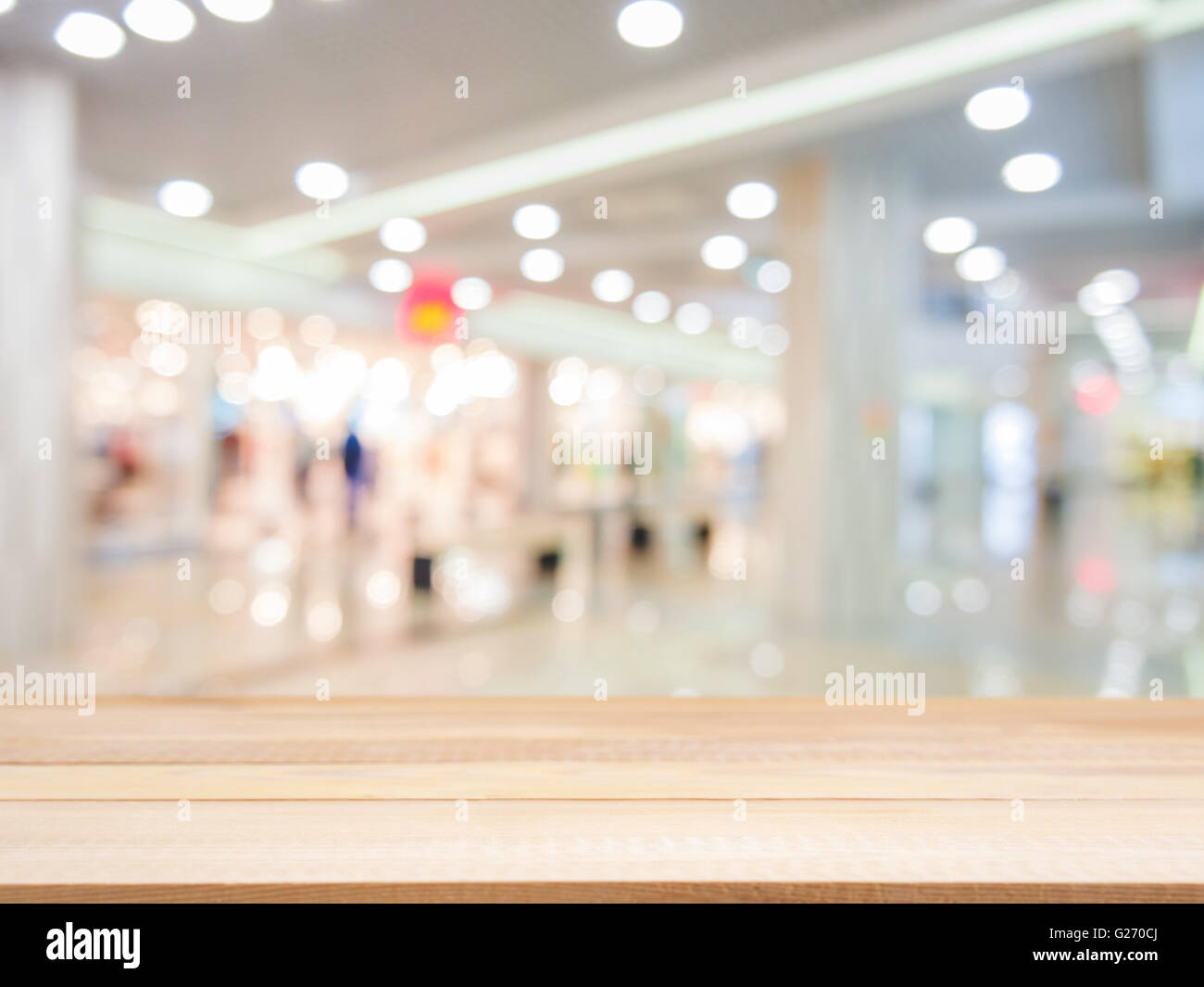 Wooden board empty table in front of blurred background. Perspective light wood over blur in shopping mall - can - Stock Image