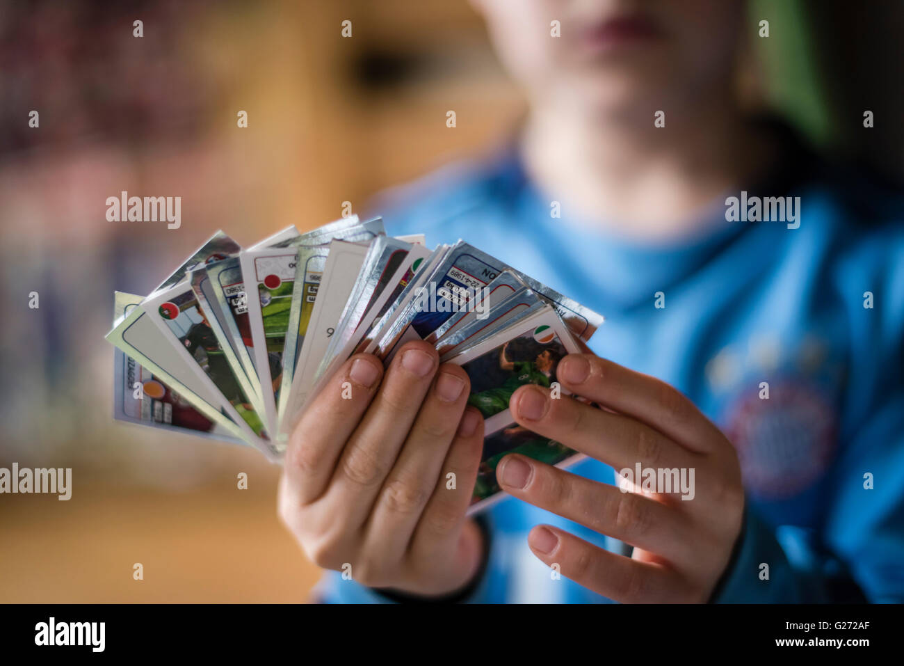 An 8 year old boy is showing his Panini football trading cards before pasting them into his sticker collection scrapbook. - Stock Image