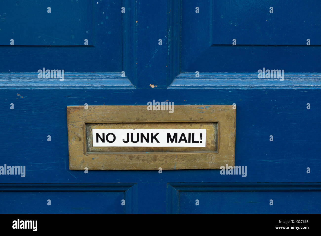 'No Junk Mail' sticker on brass letterbox on blue painted front door - Stock Image