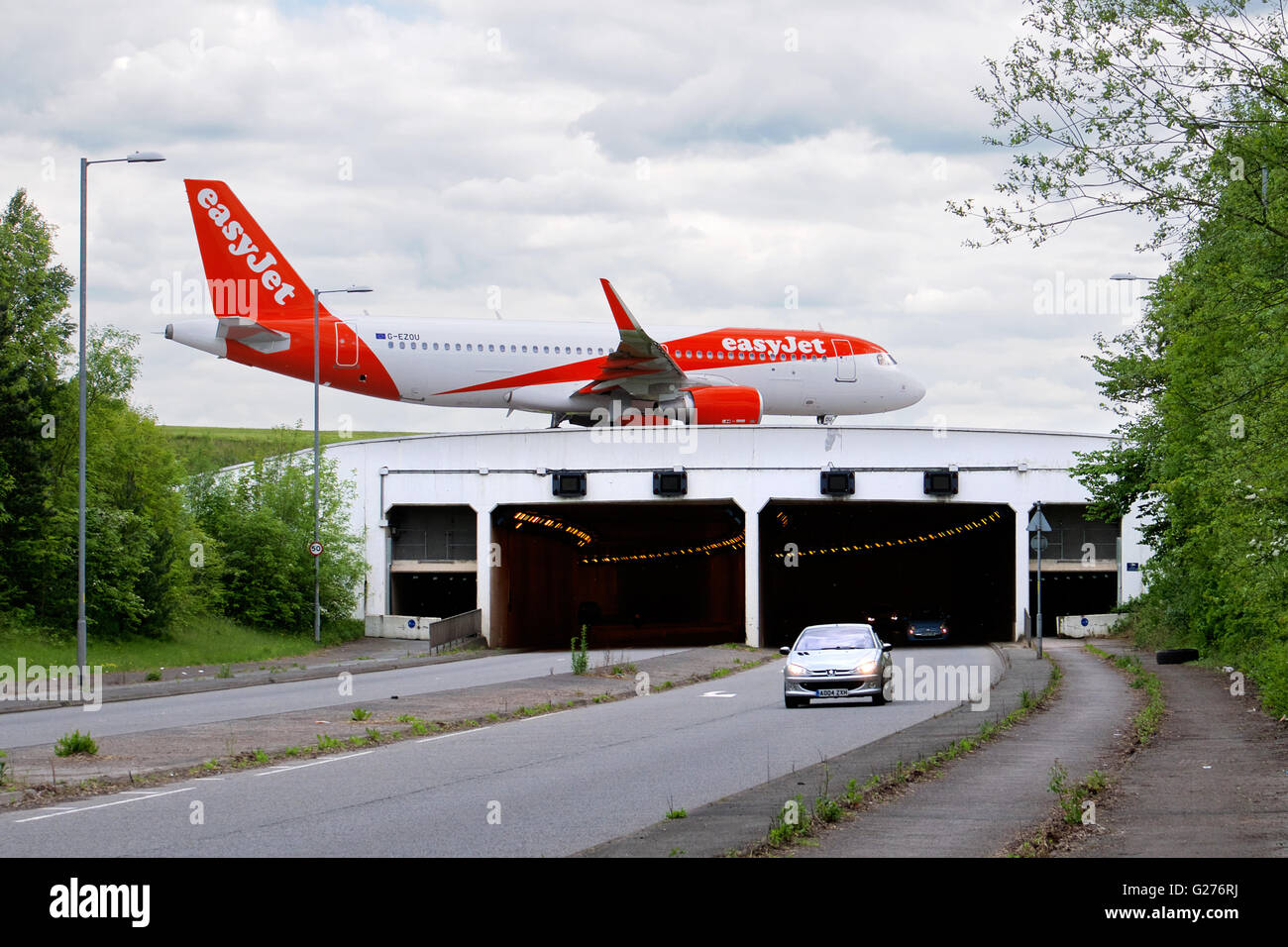 Easyjet plane taxiing over the A538 (Wilmslow Road) at Manchester's Ringway Airport, England - Stock Image