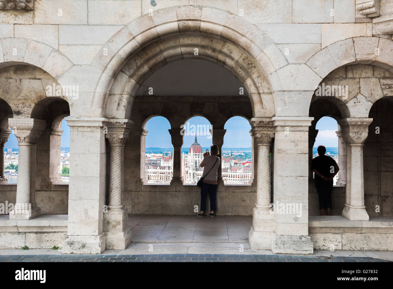 Budapest tourist, a woman tourist in a cloister inside the Fishermen's Bastion in the Var area of Budapest snaps - Stock Image