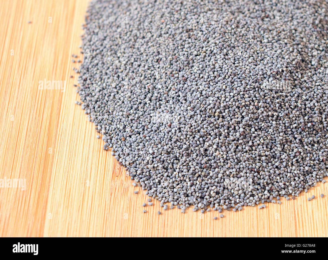 Pile of poppy seeds isolated on wooden background - Stock Image