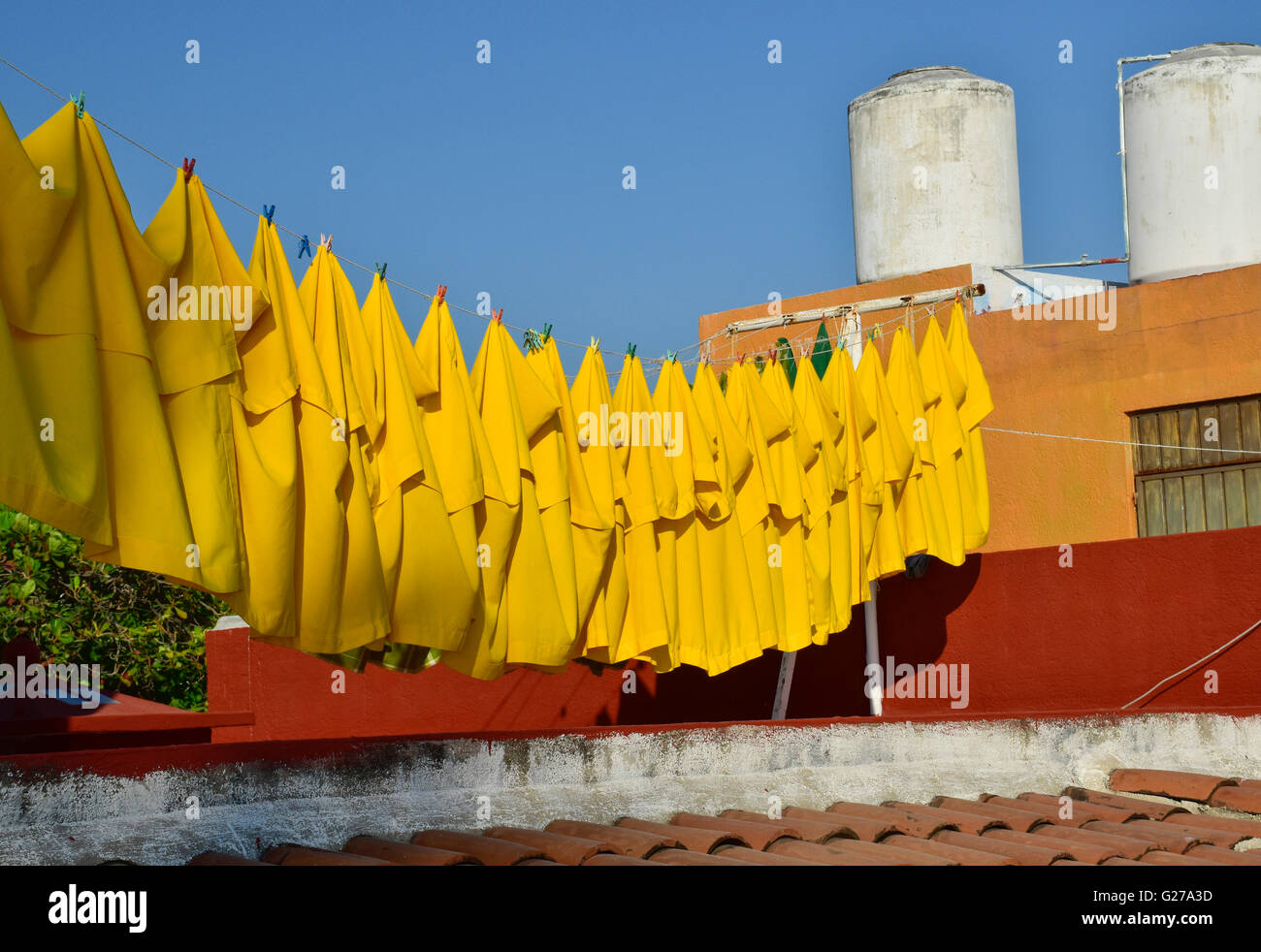Yellow tablecloths on clothesline. - Stock Image