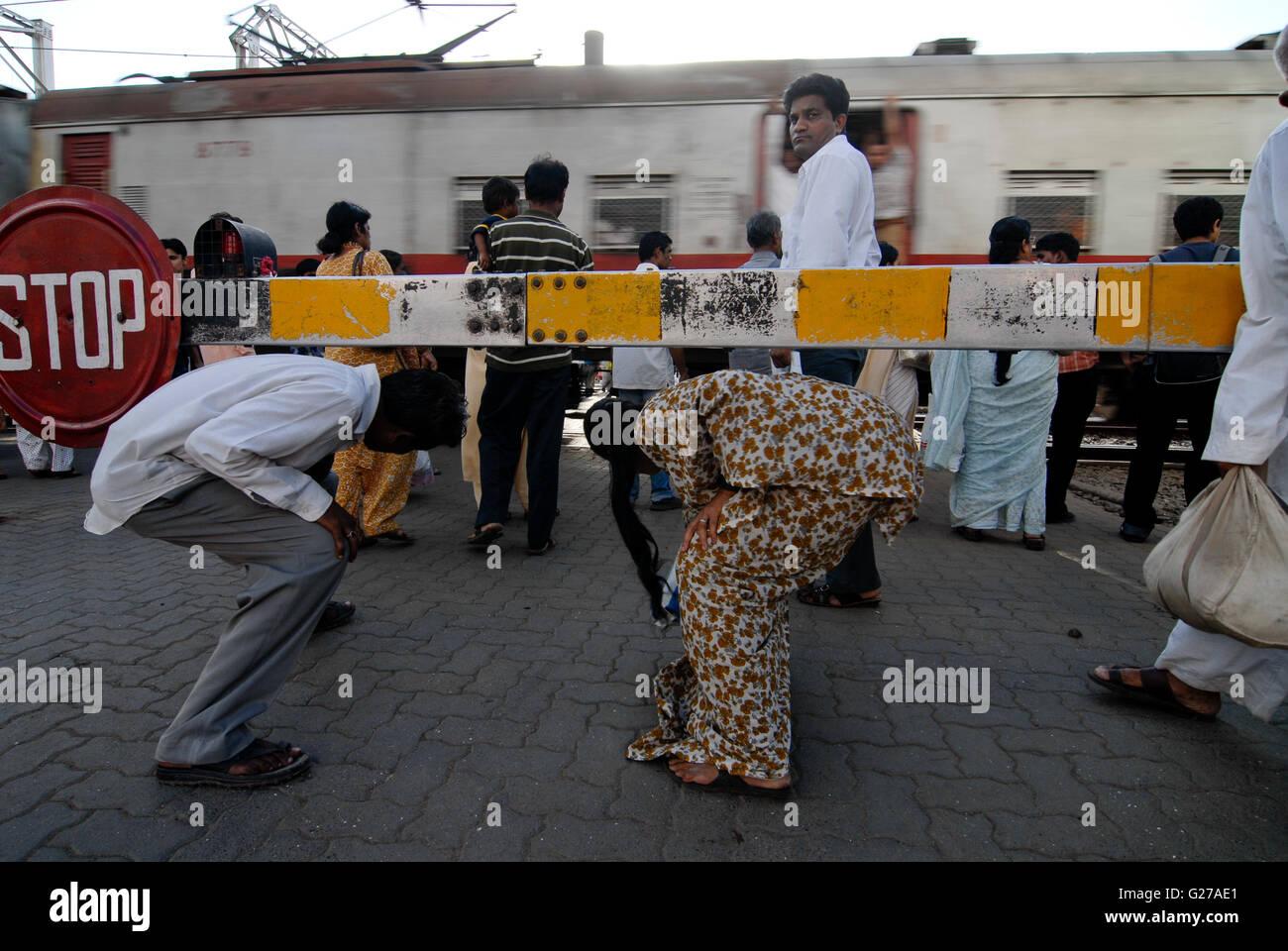 INDIA Mumbai Bombay, pedestrians cross a closed railway barrier of city train line of western railways, daily crowd Stock Photo