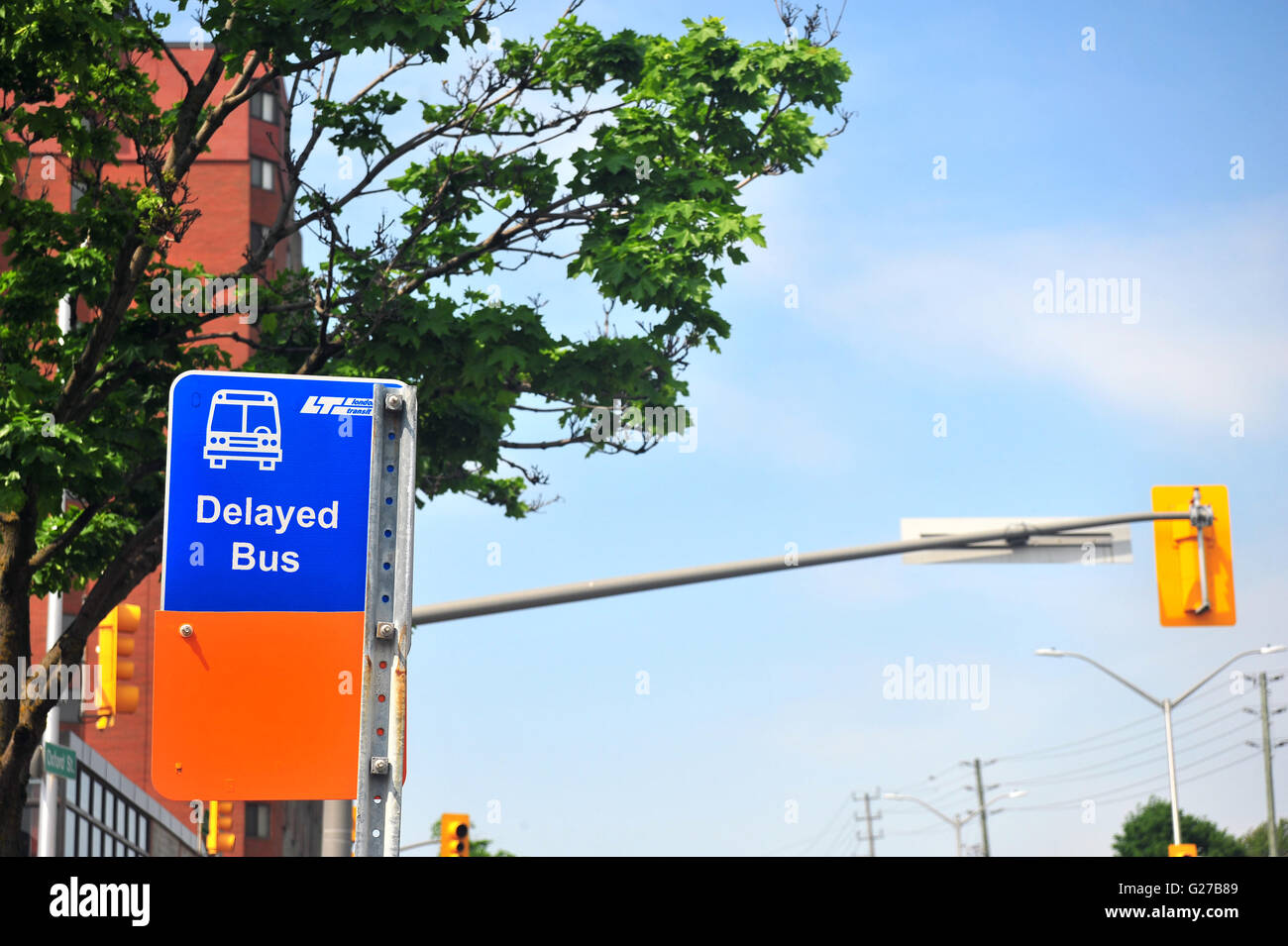 A bus sign with Delayed Bus written on it in London, Ontario in Canada. - Stock Image