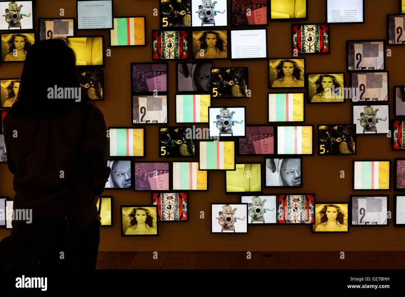 Woman looking at a collage of digital images on LCD screens, Mashup: Roots of Modern Culture exhibit, Vancouver - Stock Image