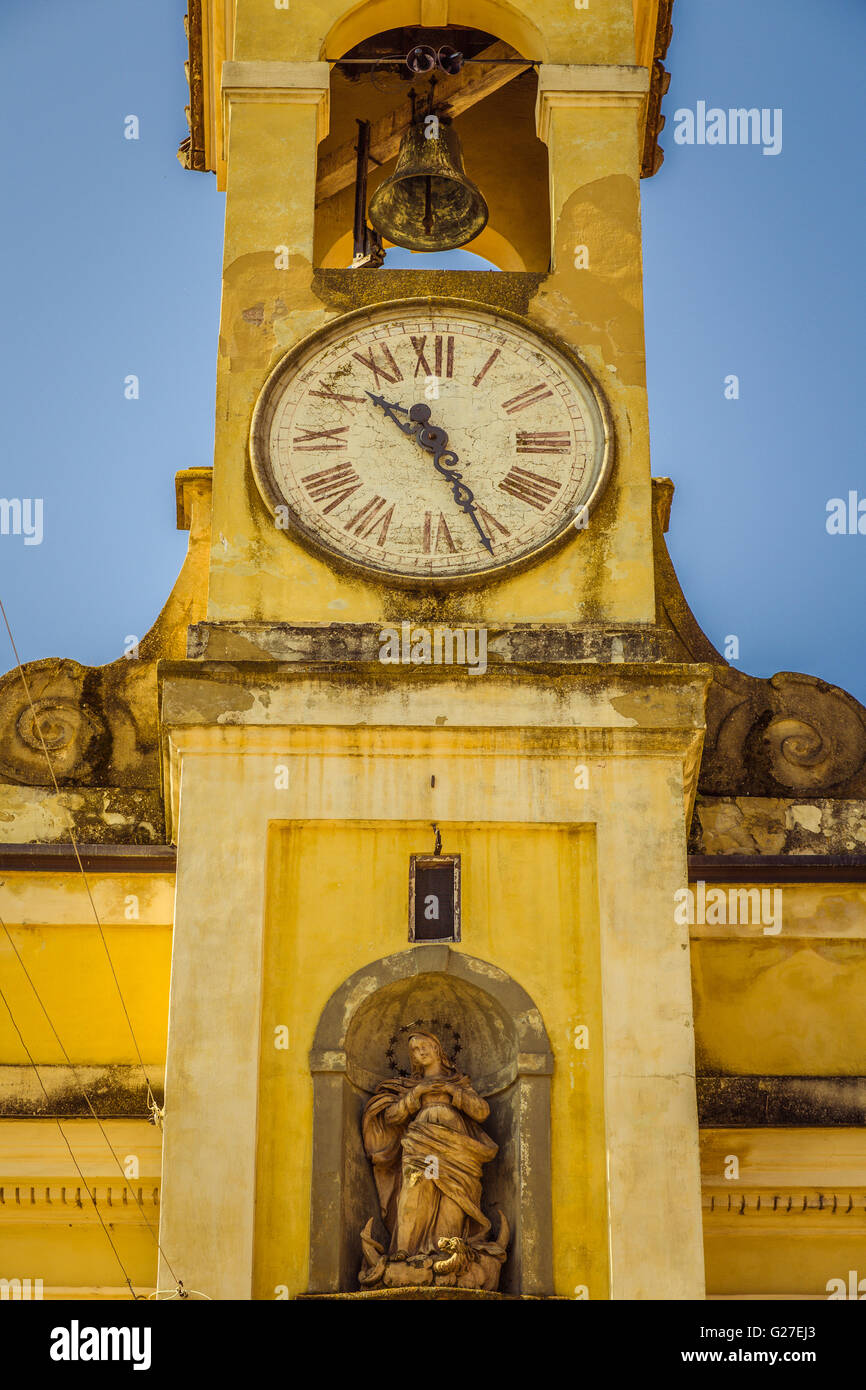 bell tower of Catholic church with clock and statue of the Blessed Virgin Mary - Stock Image