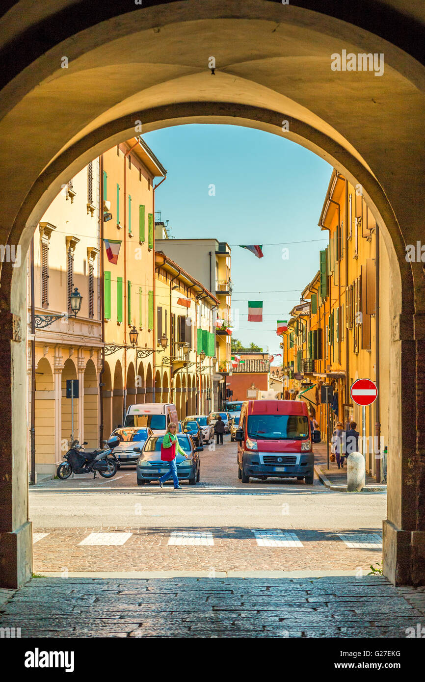 old city street with colorful houses and waving Italian flags seen through the archway of a castle - Stock Image
